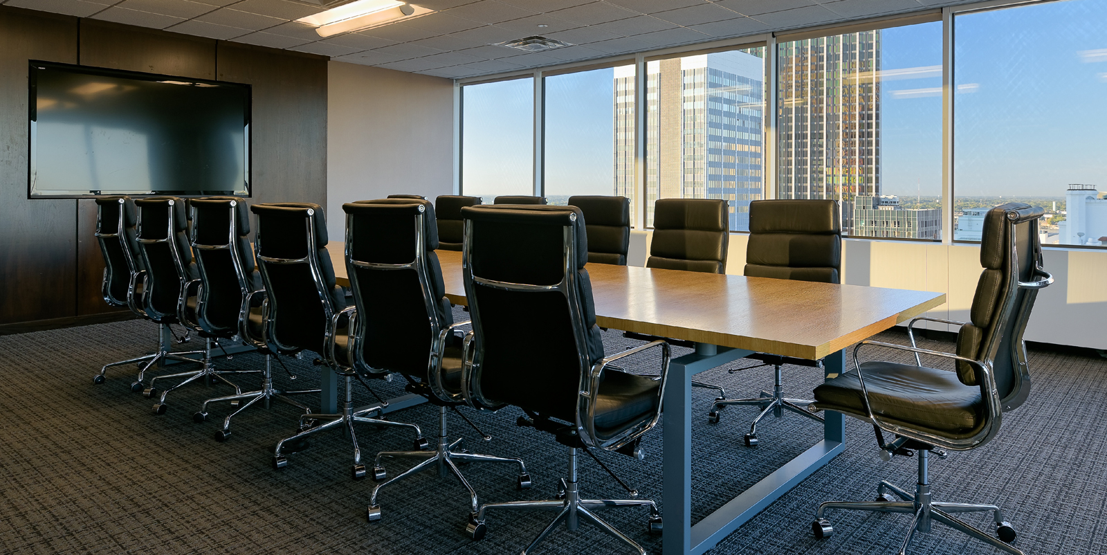 Modern conference room with ample seating and a large flat screen TV, looking out to the city below