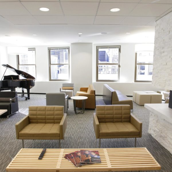 A tenant lounge area with chairs, tables and a piano inside the historic Wrigley Building in Chicago, scaled.
